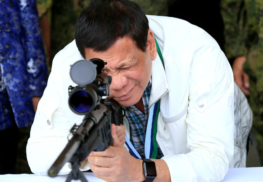 Philippines President Rodrigo Duterte checks the scope of a 7.62mm sniper rifle during the turnover ceremony of China's urgent military assistance.