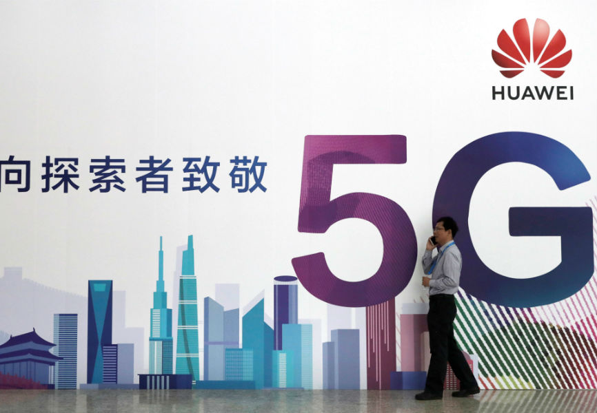 A man talks on his phone beside a Huawei billboard featuring 5G technology at the PT Expo in Beijing. REUTERS.
