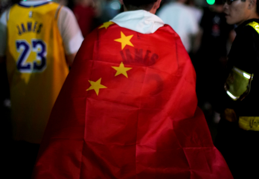 A basketball fan wraps himself in a Chinese flag before an NBA exhibition game between the Brooklyn Nets and Los Angeles Lakers in Shanghai. REUTERS.