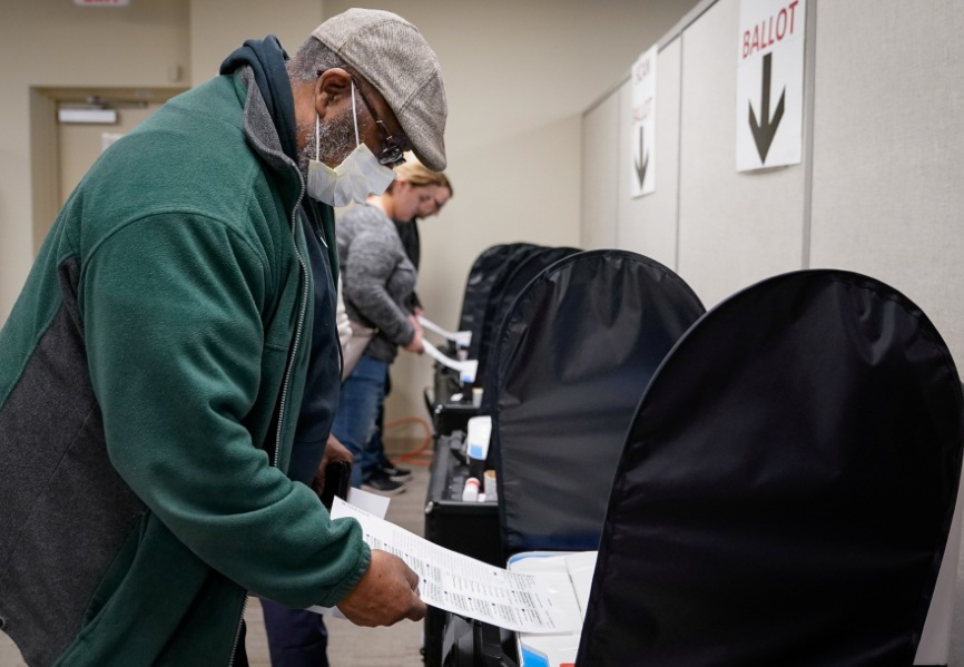 A voter wearing a protective face mask casts a ballot in the United States. REUTERS.